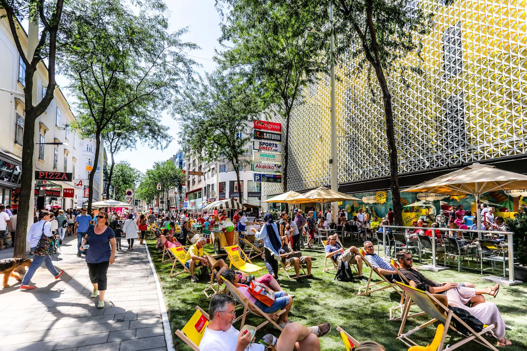 Menschen sitzen auf Grünstreifen auf der neuen Mariahilfer Straße.