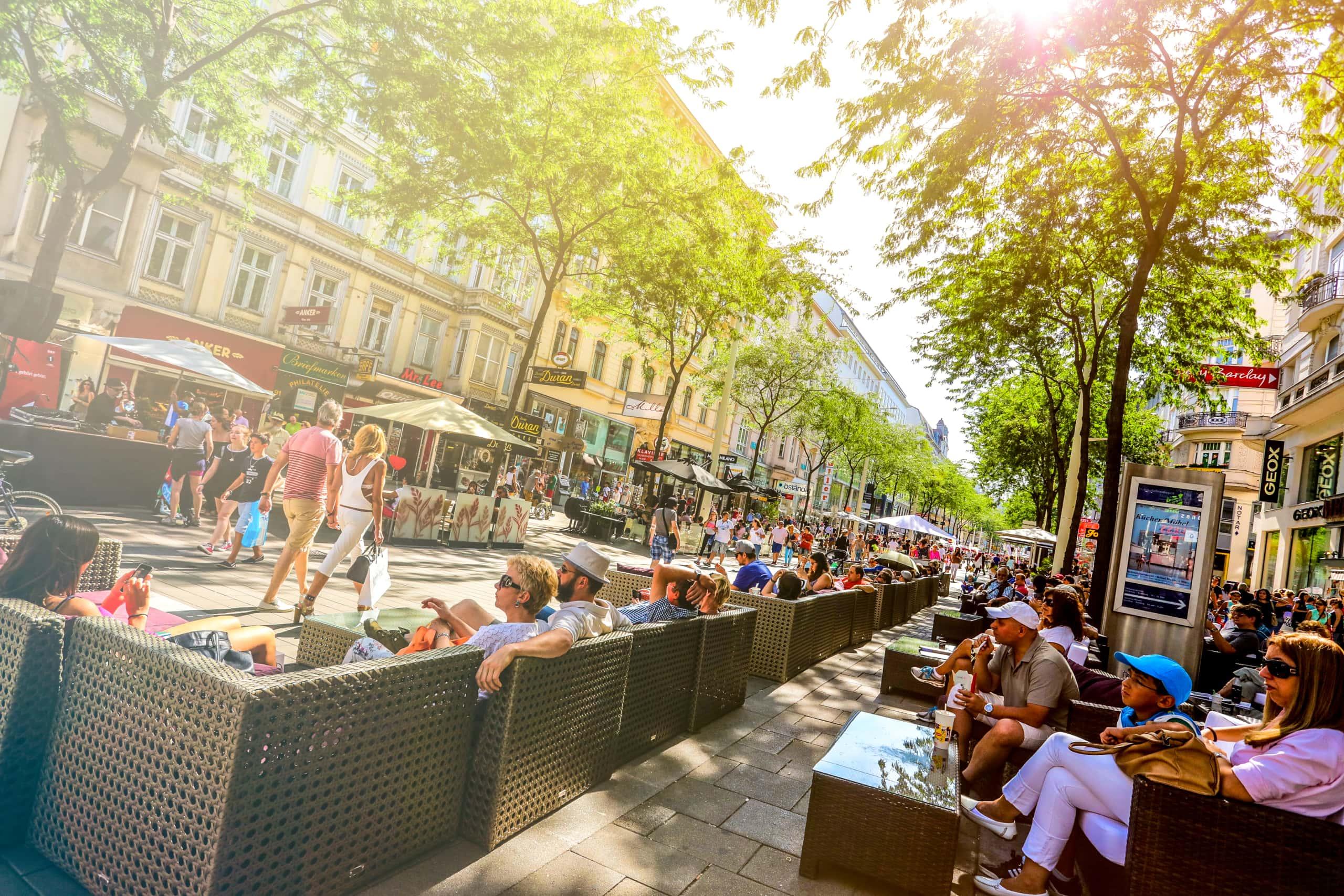 Menschen sitzen entspannt auf der Mariahilfer Straße.
