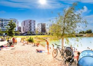 Menschen genießen die Sonne am See von der Seestadt-Aspern.