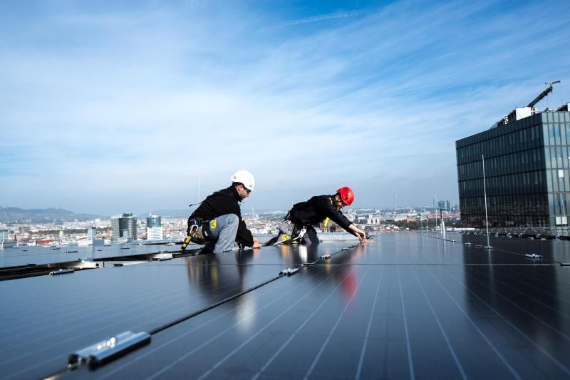 Zwei Menschen installieren eine Solaranlage auf einem Dach.