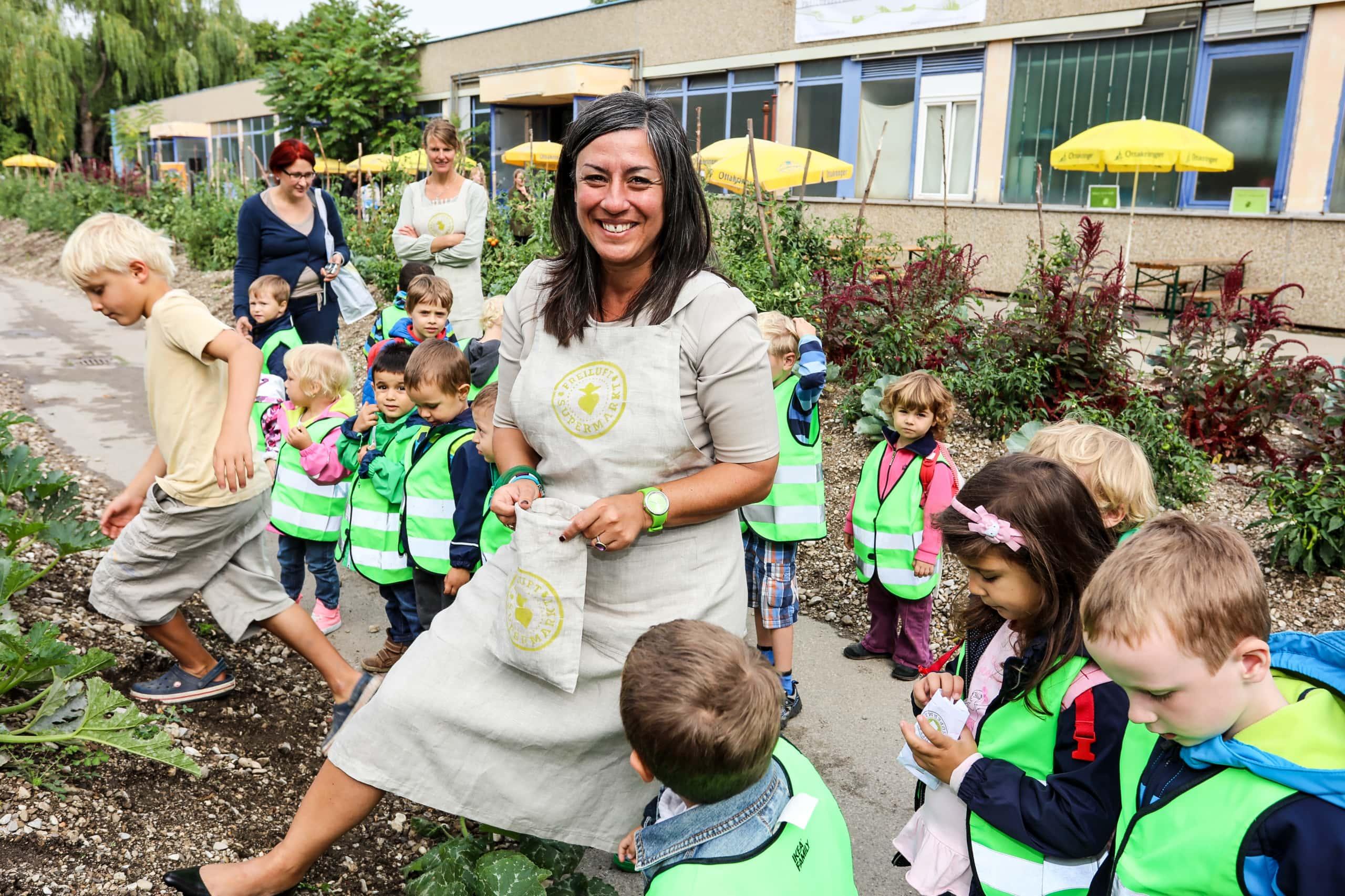 Maria Vassilakou steht mit Kindern vor einem Urban Garden.
