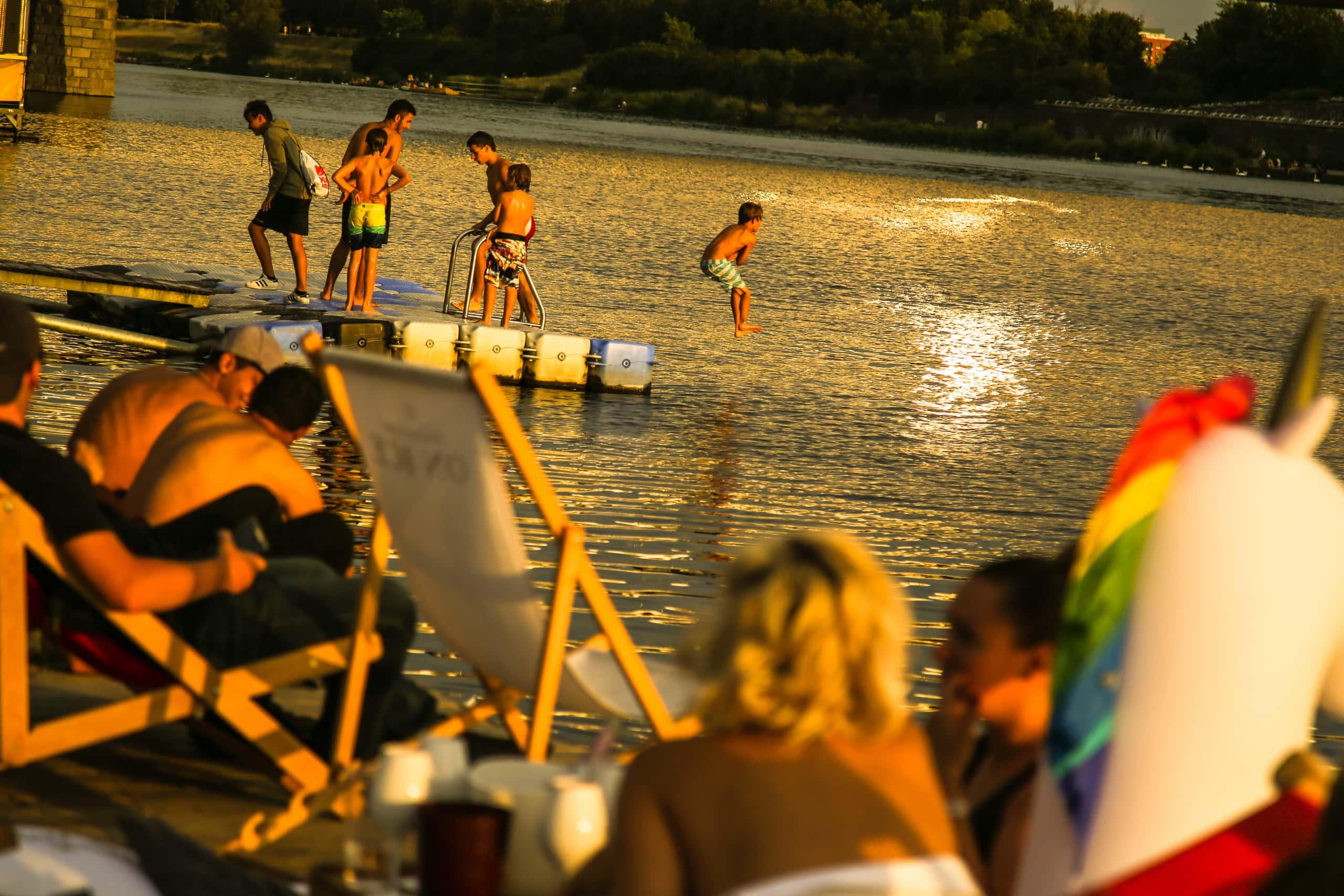 Menschen an der Donau bei Sonnenuntergang.